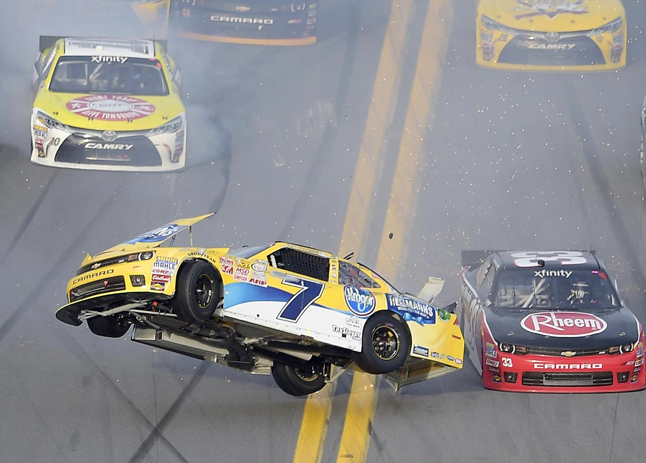 Regan Smith flips on the front stretch after being involved in a multi-car accident, as Austin Dillon (33) drives past during a NASCAR Xfinity series auto race at Daytona International Speedway.