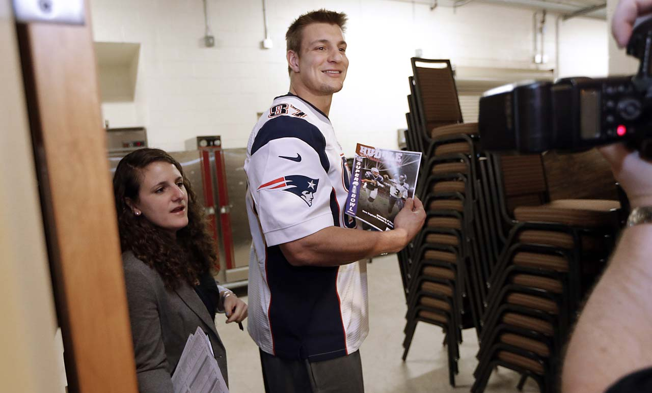 Patriots tight end Rob Gronkowski poses for a photo with a magazine he was given as he leaves a news conference Wednesday.