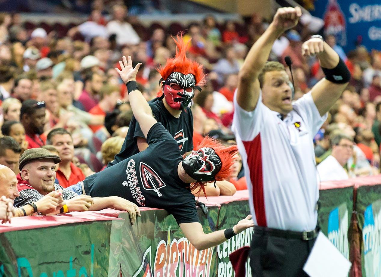 Masked Cleveland Gladiators fans behind Orlando Predators coach Rob Keefe during their game against the Orlando Predators.