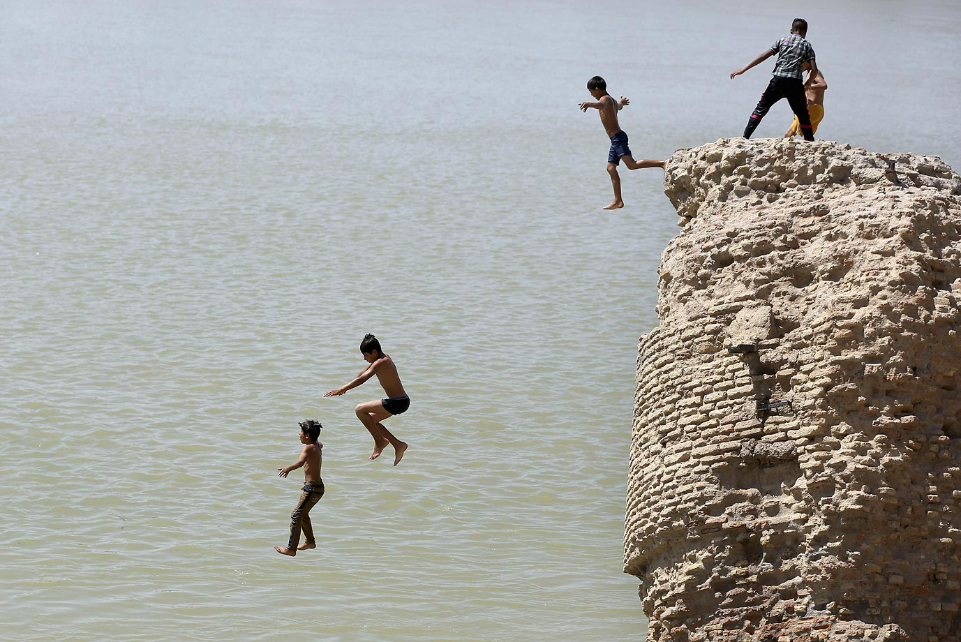 Children jump off the ruin of an old building into the Tigris River to beat the heat in Baghdad, Iraq.