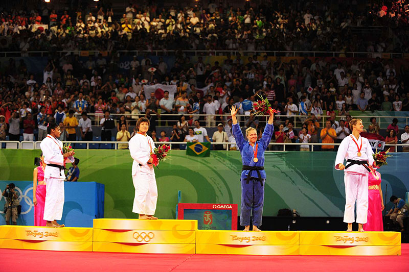 Ronda Rousey stands on the podium after winning bronze at the 2008 Olympics.