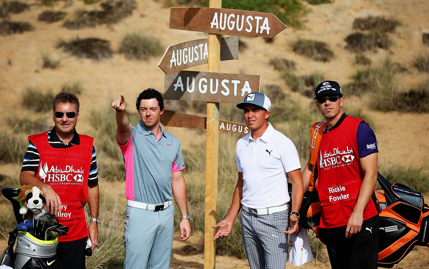 Rory McIlroy and Rickie Fowler take some advice from caddies JP Fitzgerald (far left) and Joe Skovron during a photocall prior to the start of the Abu Dhabi HSBC Golf Championship.  We think Augusta is that way...