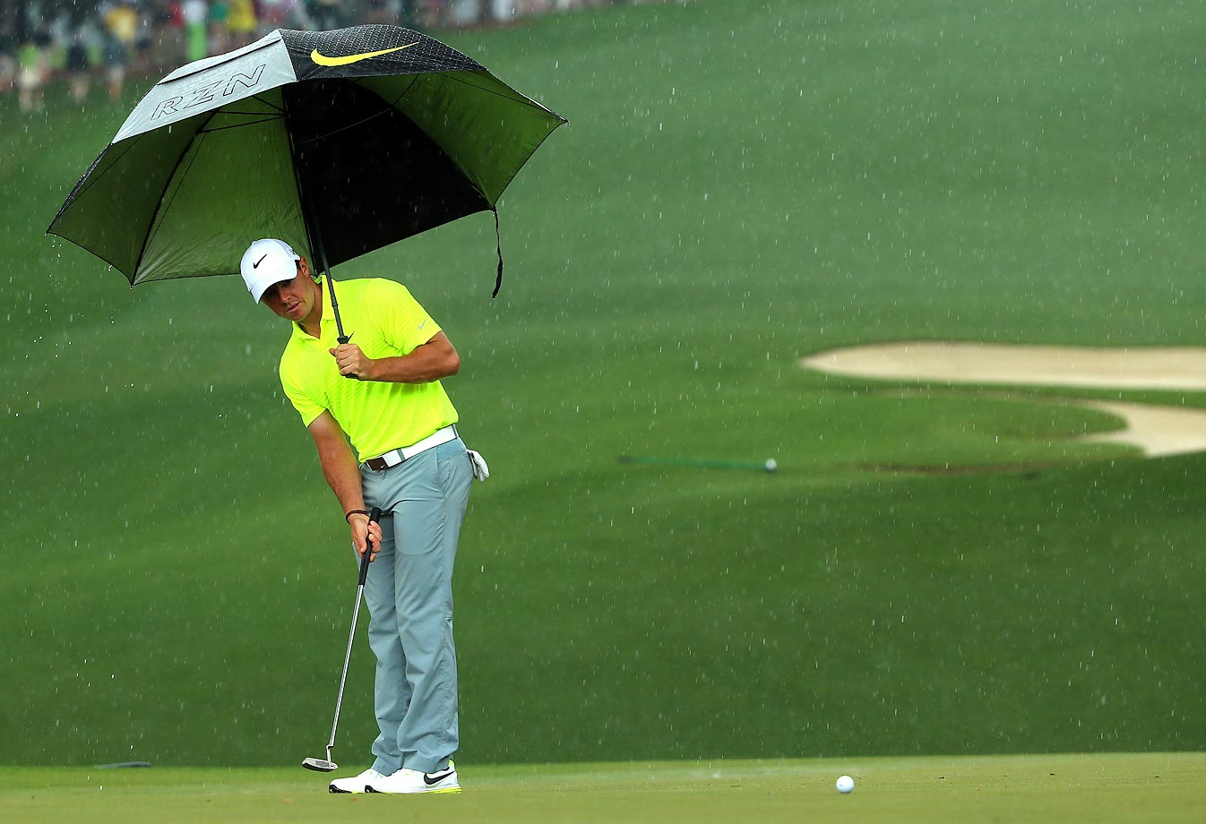 Rory McIlroy hits a putt in the rain during a practice round at the Masters.