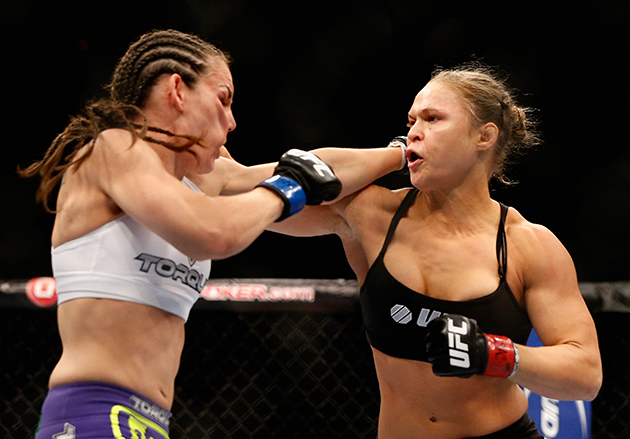 From right to left, UFC Women's Bantamweight champion Ronda Rousey punches Alexis Davis in their title fight at UFC 175 inside the Mandalay Bay Events Center in Las Vegas, Nevada.