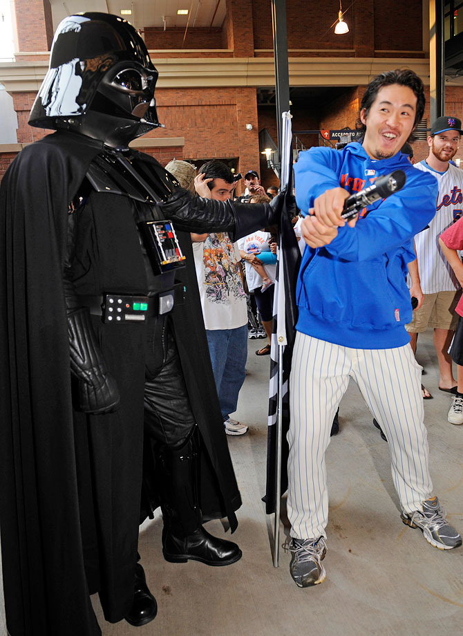 New York Mets pitcher Ryota Igarashi wields a lightsaber against a fan dressed as Darth Vader prior to the Mets game against the Washington Nationals on Sept. 13, 2011 at Citi Field in New York.