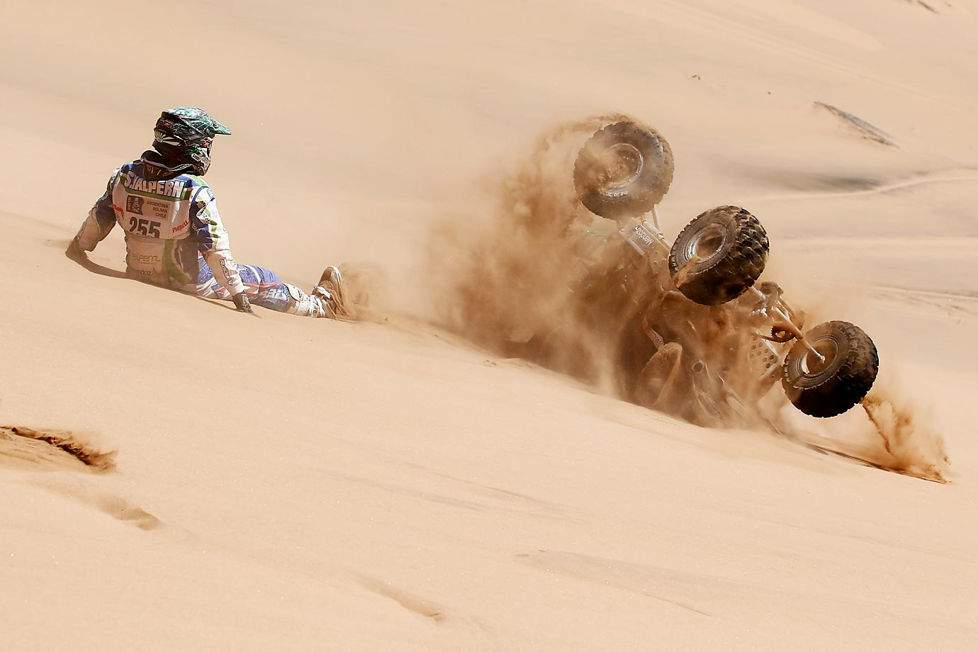 Sebastian Halpern chases his quad as it rolls down the sand dune at the Dakar Rally.
