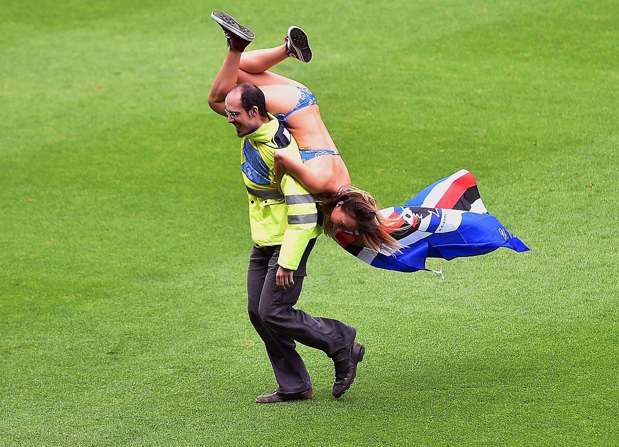 A fan of Sampdoria is carried off by a steward after running onto the pitch during the Serie A match between UC Sampdoria and SSC Napoli.