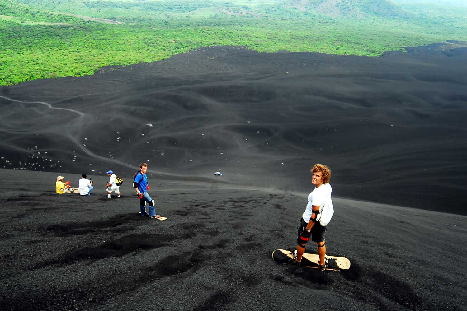 Extreme sports enthusiasts boarding down the basaltic cone of Cerro Negro Volcano in the outskirts of Leon, Nicaragua.
