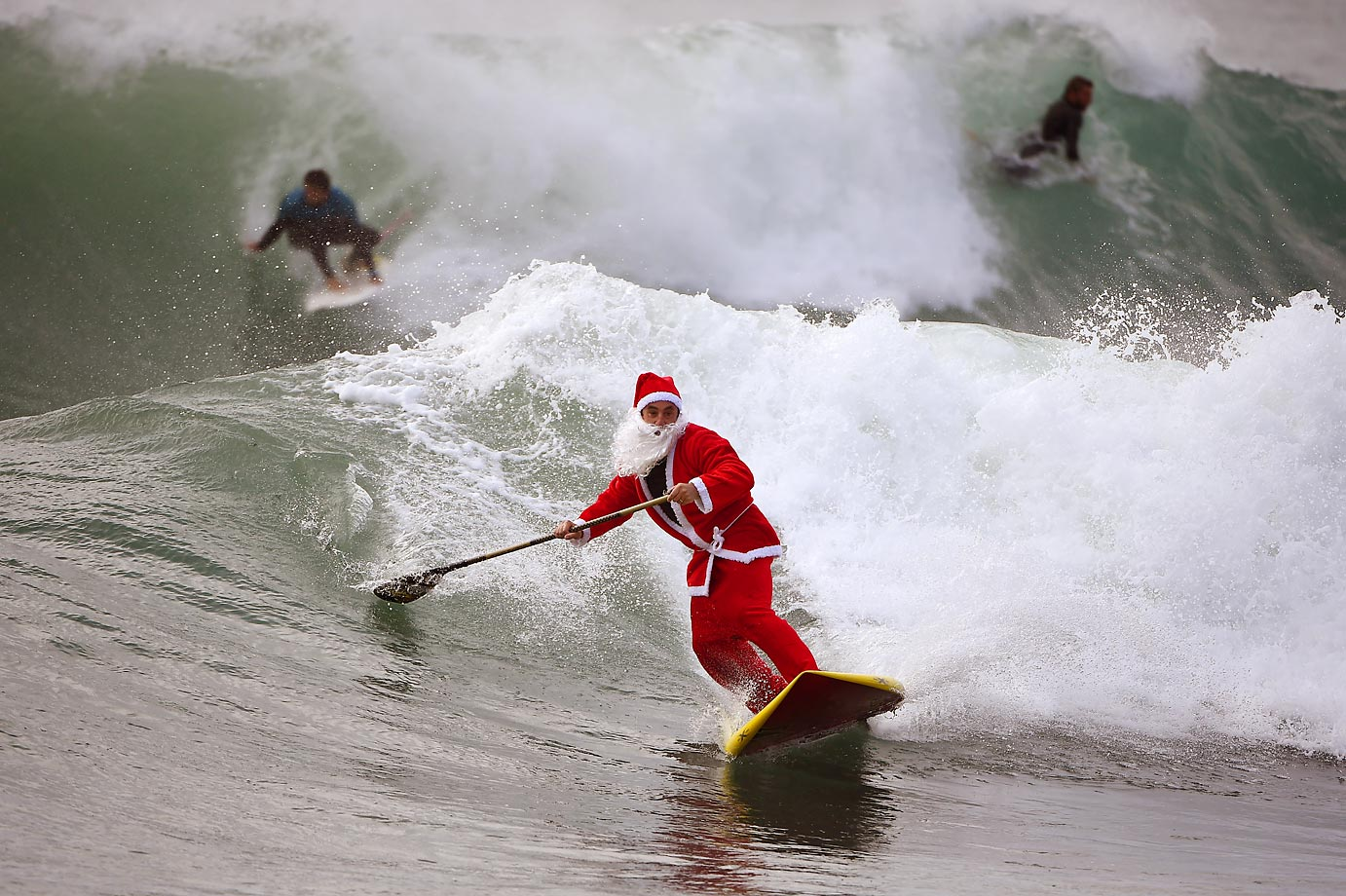 Santa impressively rides a wave on a stand up paddle board in Varazze, Italy.
