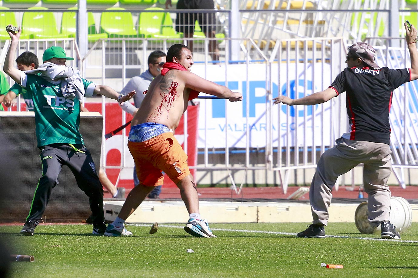Soccer fans of Santiago Wanderers, left, fight with a fan of the Colo-Colo soccer team before the start of their teams' local match in Valparaiso, Santiago, Chile. The match was suspended after fans clashed violently on the field.