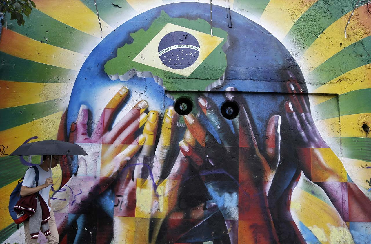 A pedestrian passes a graffiti depicting human hands holding the earth with the Brazilian flag in Sao Paulo on June 10.