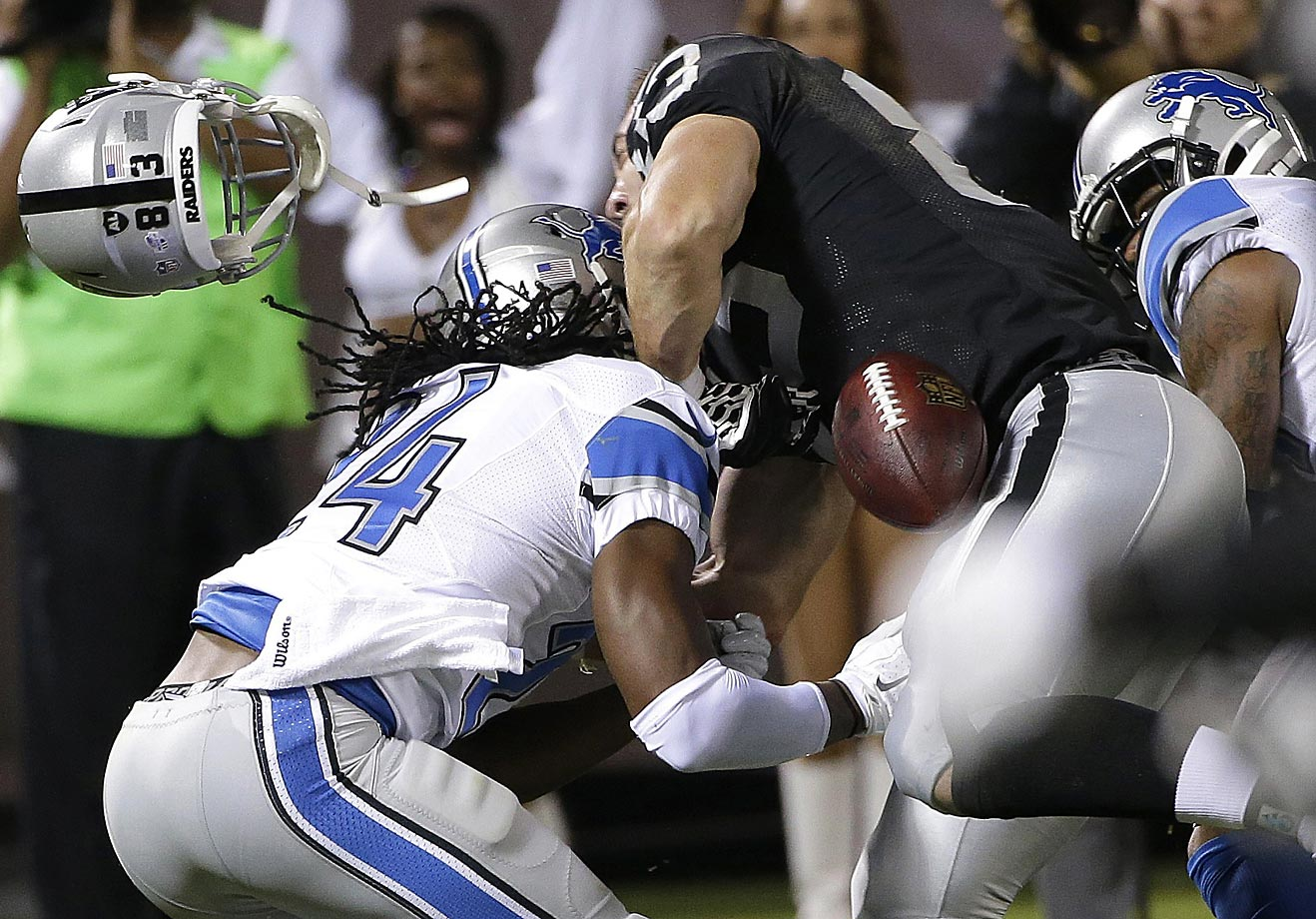 Oakland Raiders tight end Scott Simonson loses his helmet and a fumble as he's hit by Detroit Lions defensive back DeJon Gomes.