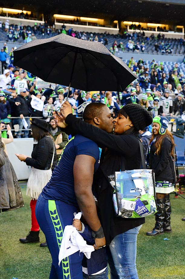 A Seattle Seahawks kiss in the rain.  How appropriate.