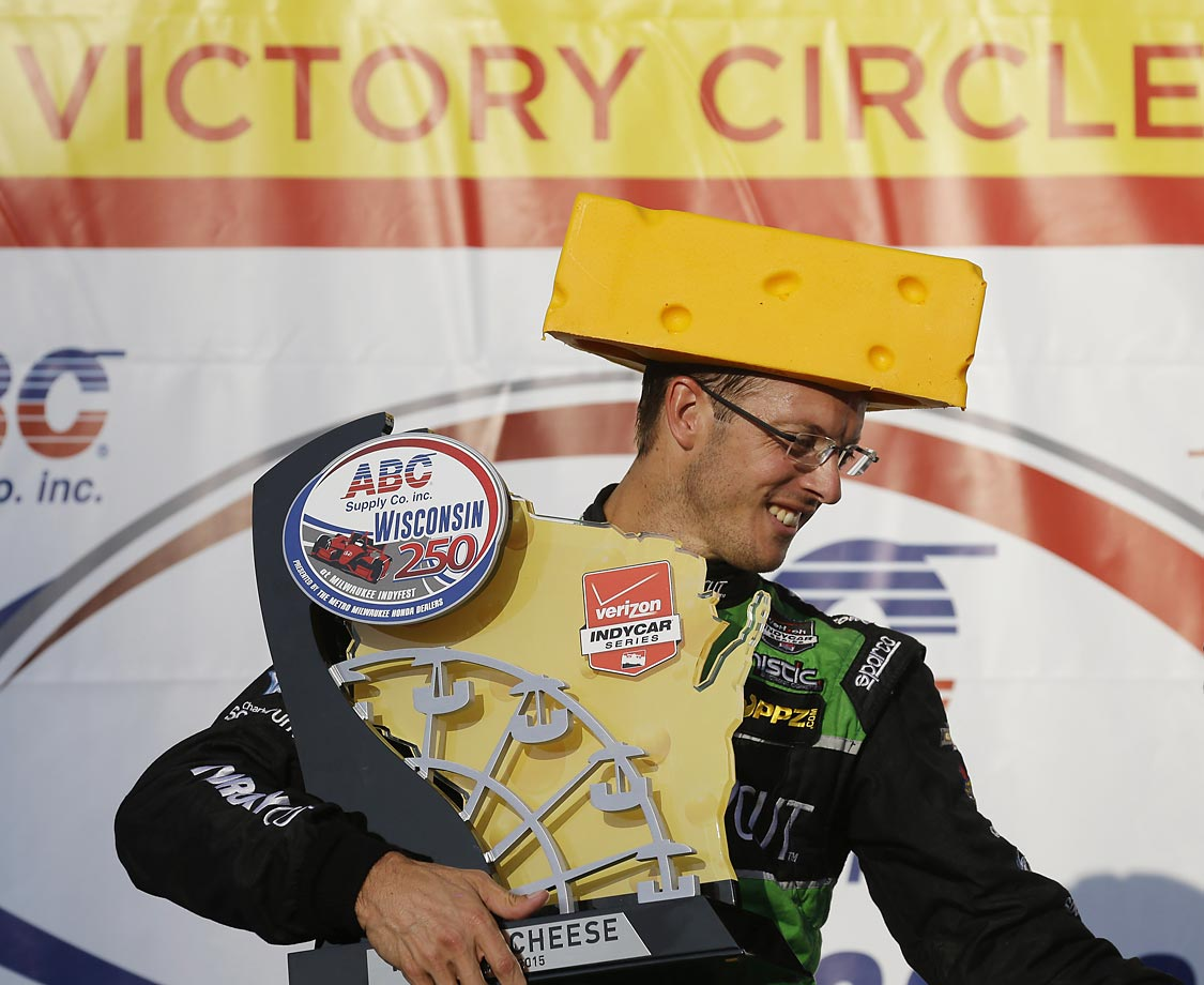 Sebastian Bourdais of France wears a cheese head hat and gets the winner's trophy after the IndyCar Series race at the Milwaukee Mile in West Allis, Wis.
