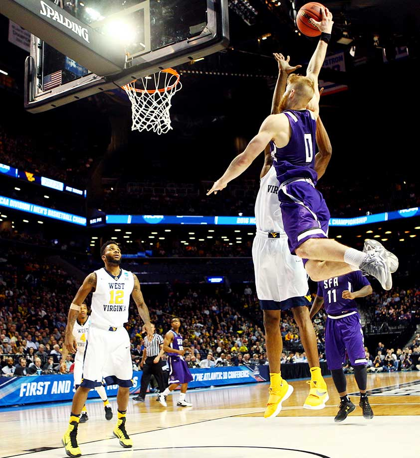 Thomas Walkup goes high for a basket on a night in which he scored 33 points as No. 14 Stephen F. Austin soundly defeated No. 3 West Virginia.