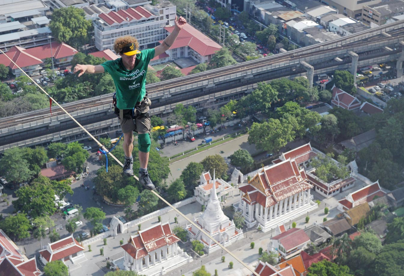 Andy Lewis of the U.S. balances as he walks on a highline from the rooftop of a building in Bangkok on July 23, 2014. Lewis set a world record after walking on a highline from the rooftop of a building to another covering a distance of 169 meters in one hour and five minutes.