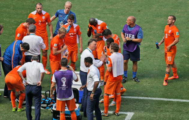 Dutch players consume drinks during a cooling break in the World Cup round of 16 soccer match between the Netherlands and Mexico at the Arena Castelao in Fortaleza, Brazil, Sunday, June 29, 2014.