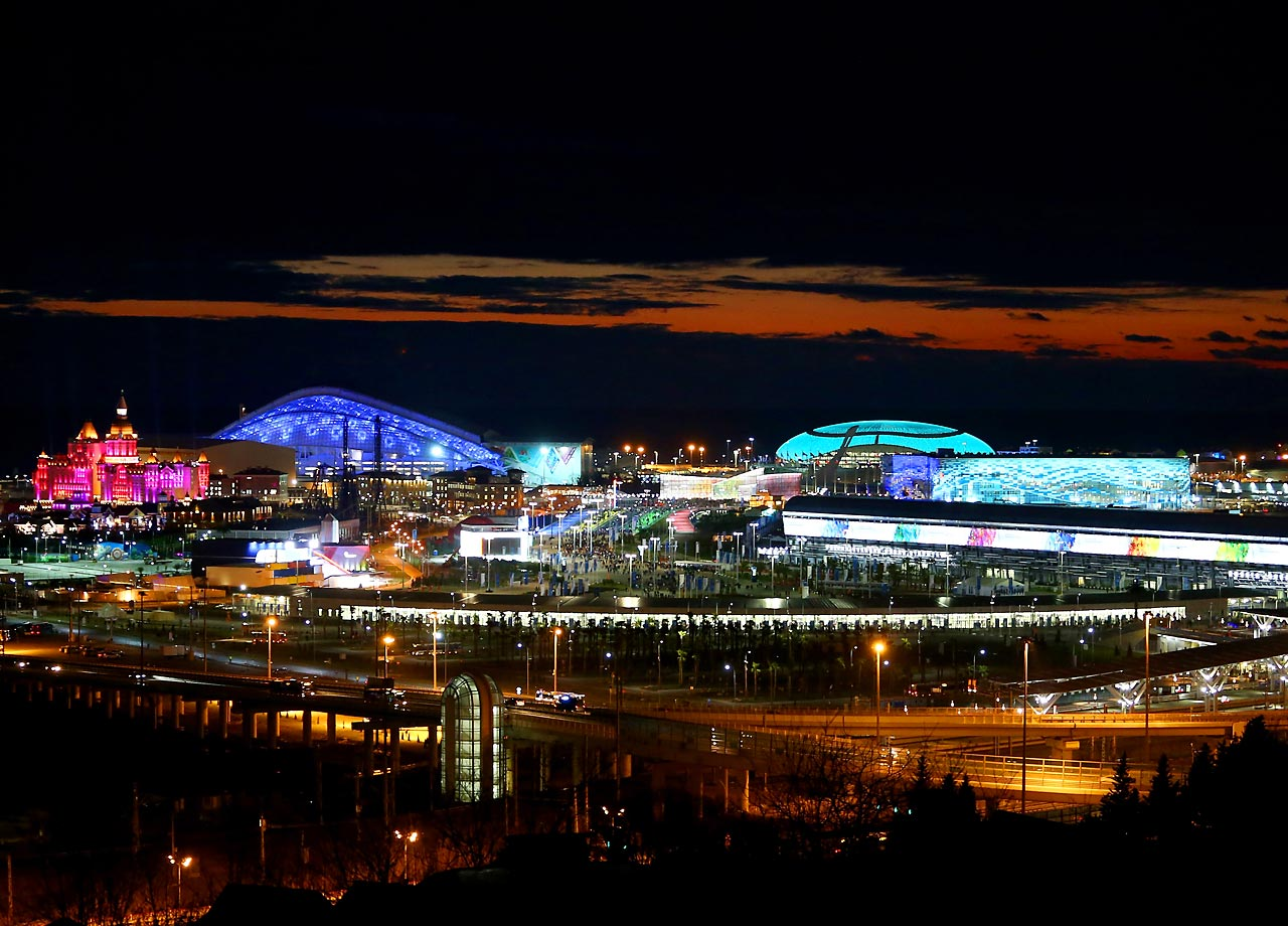 The buildings and stadia are lit up as the sun sets over the Olympic Park.