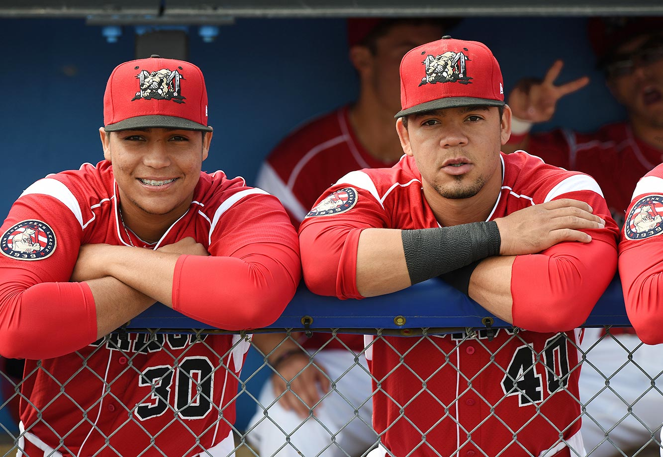 Carlos Duran and Victor Castro of the Batavia Muckdogs gets photobombed by Aaron Blanton, who's sitting on the bench.