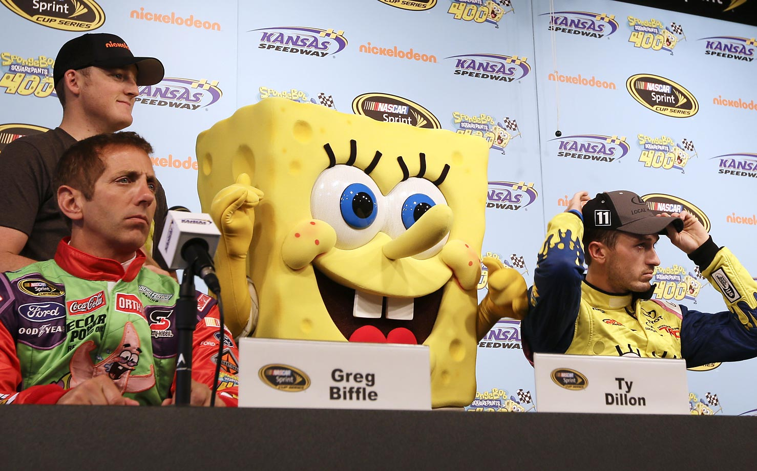 Greg Biffle (left), SpongeBob, and Ben Kennedy at a news conference for the Sprint Cup Series auto race at Kansas Speedway. The race is named the SpongeBob Square Pants 400.