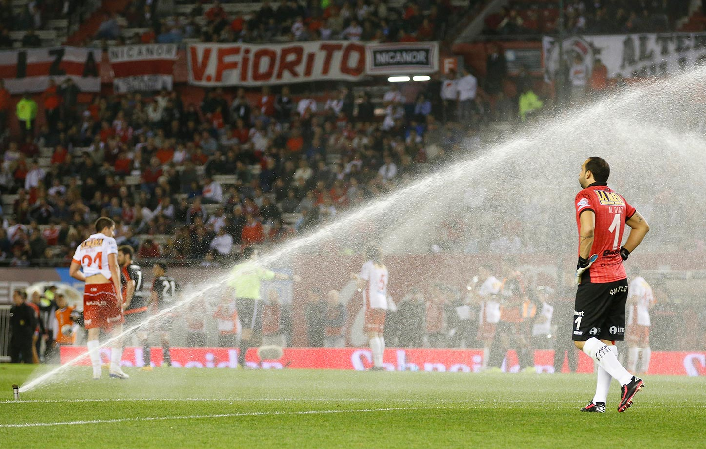 Marcos Diaz, the goalkeeper of Huracan, gets sprayed by the sprinklers that were mistakenly turned on during a match against River Plate in Buenos Aires.