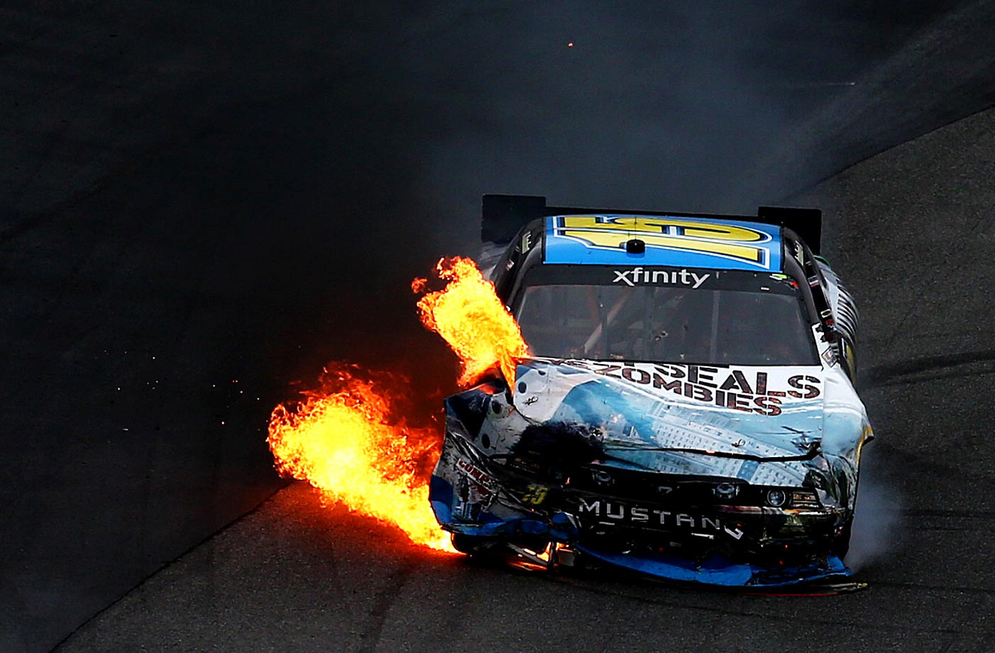 Flames pour from the Navy SealsVsZombies.com Ford, driven by Stanton Barrett during the NASCAR XFINITY Series Hisense 200.