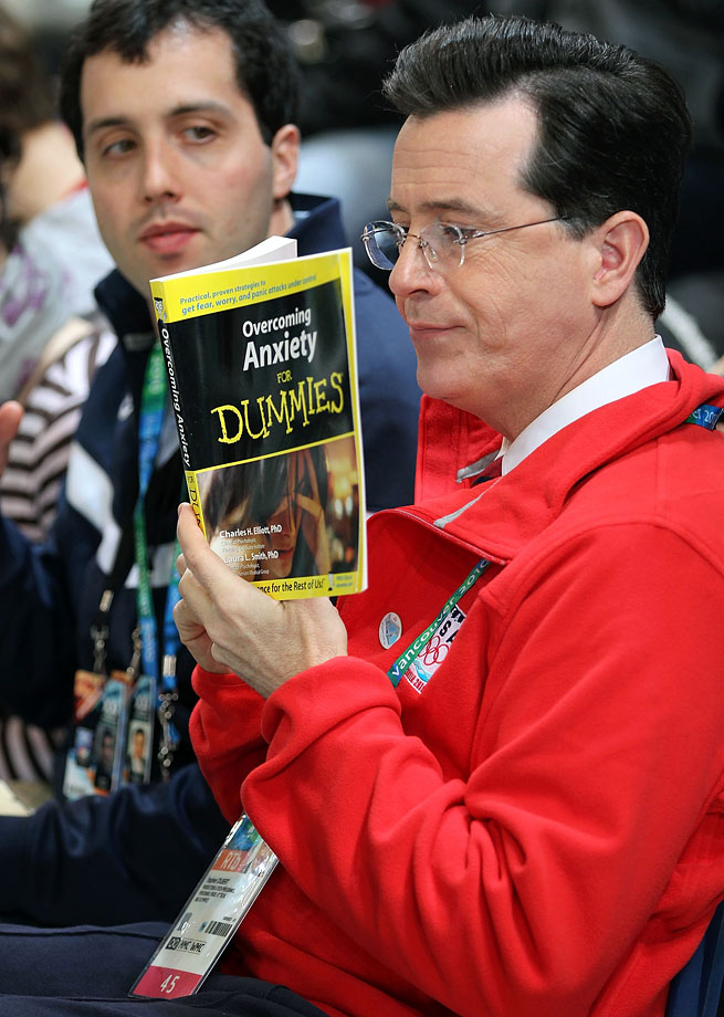 "Stephen Colbert reads a copy of ""Overcoming Anxiety for Dummies"" prior to the start of the men's speed skating 1000 meter finals on Feb. 17, 2010 during the Winter Olympics in Vancouver, Canada."