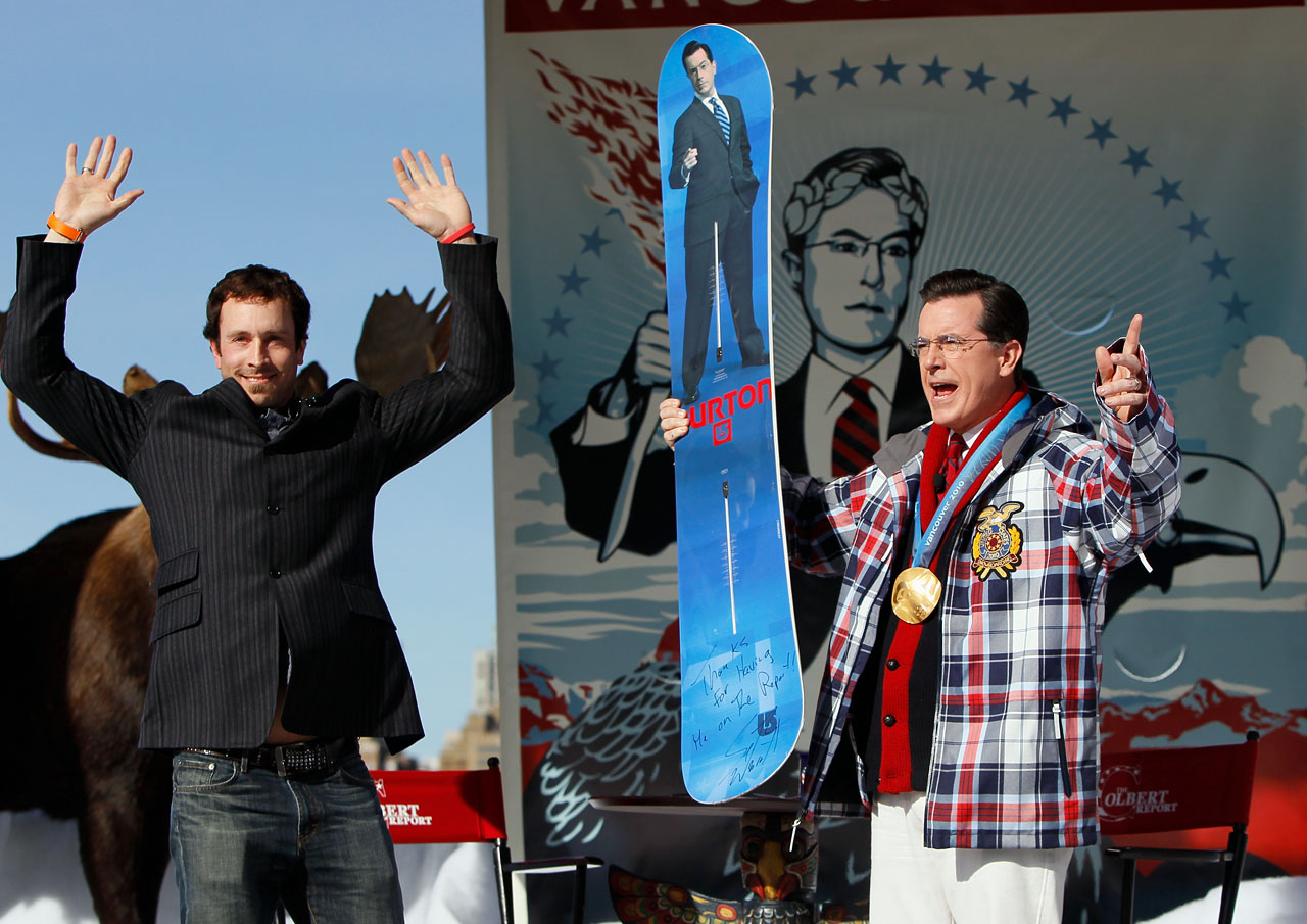 Stephen Colbert reacts after receiving a custom made Burton snowboard from Olympic gold medalist Seth Wescott of the United States while taping an episode of The Colbert Report at Creekside Park on Feb. 18, 2010 in Vancouver, Canada.