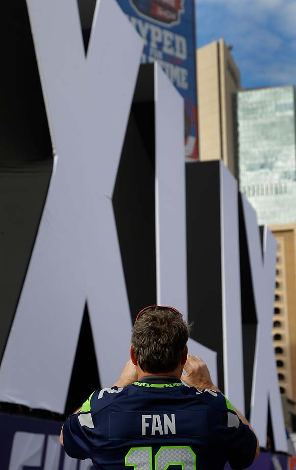 A fan takes a photo of Roman numerals erected in downtown Phoenix for Super Bowl XLIX.