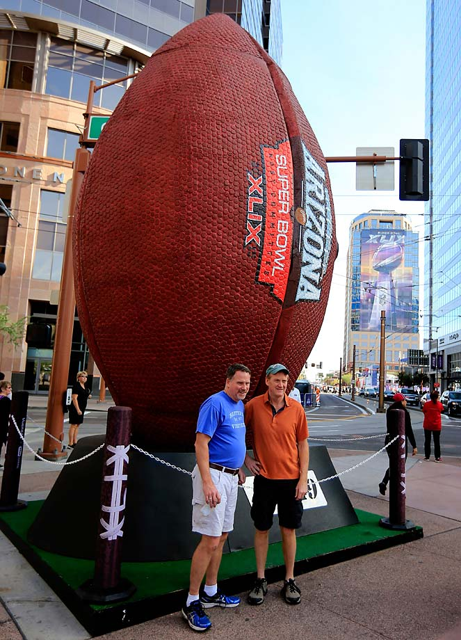 People pose in front of a giant football in a fan zone for Super Bowl XLIX.