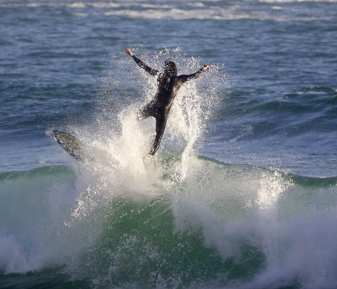 A surfer crashes through a wave at Camps Bay beach near the city of Cape Town, South Africa, Tuesday, July 29, 2014. Madagascar is the 14th country in Africa to become a member of the International Surfing Association, joining South Africa, Namibia, Senegal, Nigeria and other countries on the continent.