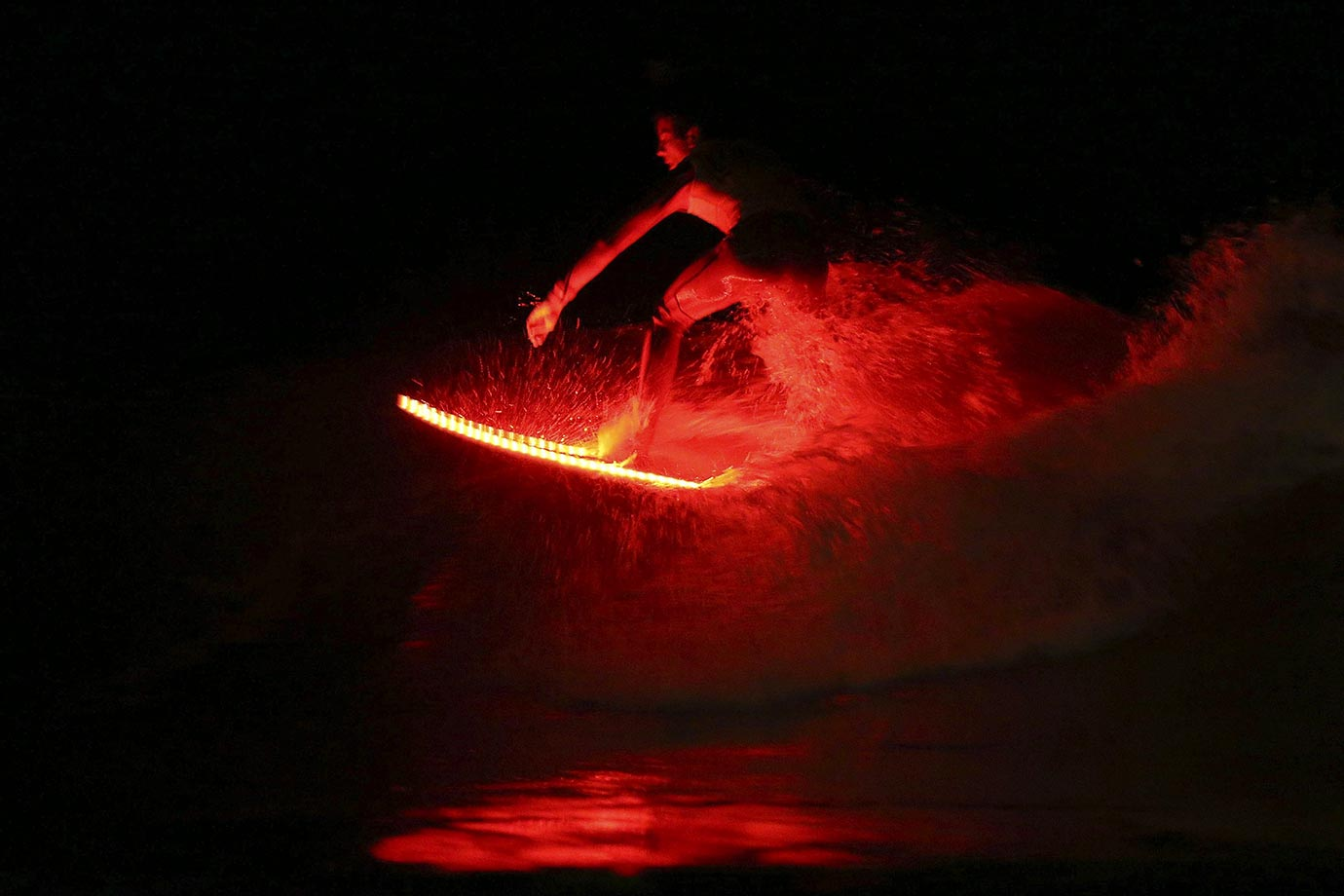A surfer rides a wave on an illuminated surf board during a night surfing event in Nigran, Pontevedra, northwestern Spain.