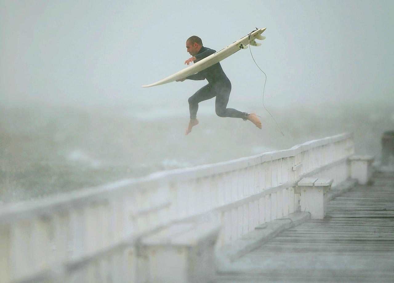 A surfer jumps off a pier into Port Phillip Bay to take advantage of the waves as a storm lashes the Melbourne area.