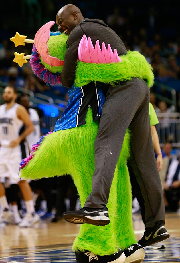 Terrell Owens get a hug from the Orlando Magic mascot at a Memphis Grizzlies game.