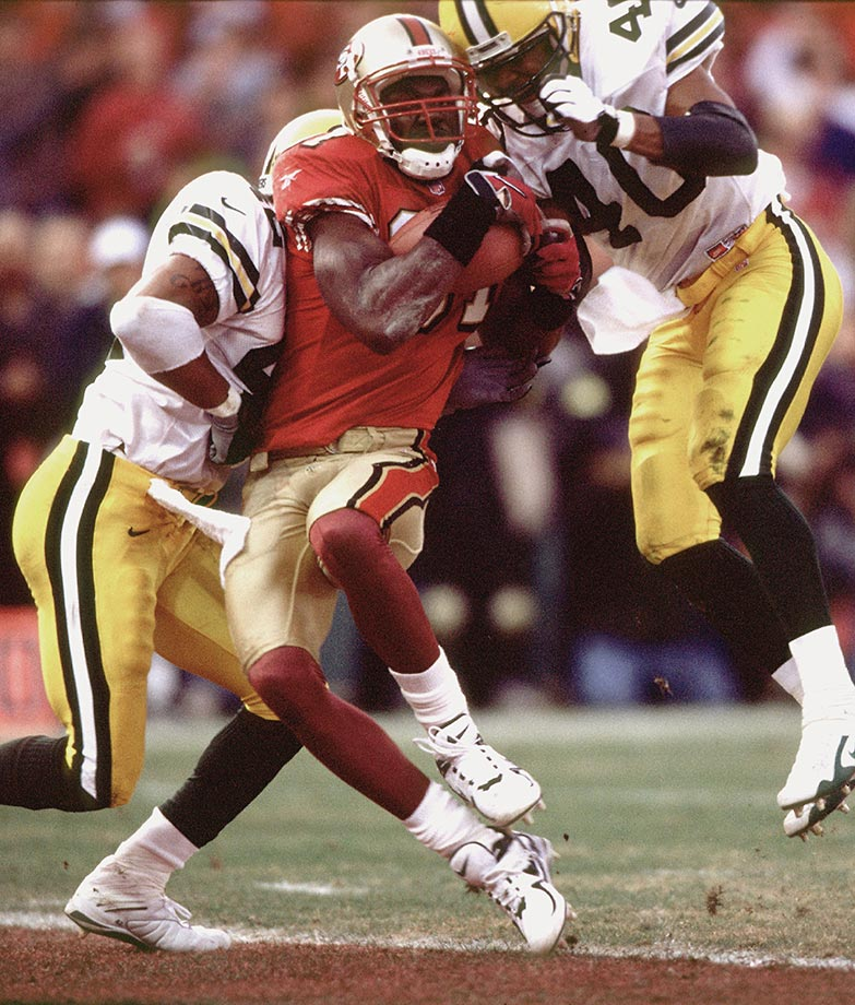 1998: 49ers Terrell Owens hangs on to winning 25-yard TD pass in the final eight seconds despite being clobbered by three Packers defenders in the first-round playoff game.