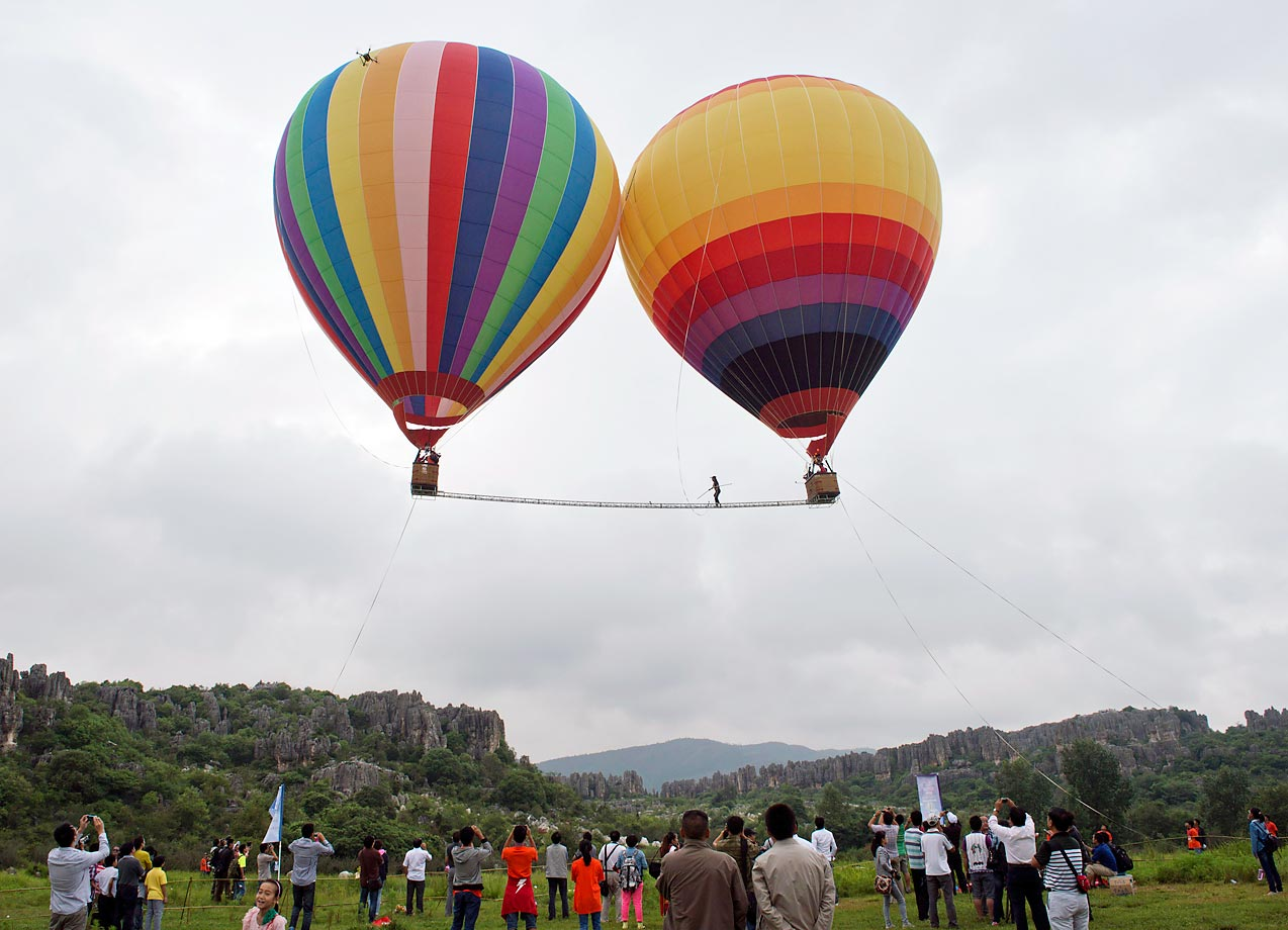 Exelon Kyle walks between two hot air balloons in Kunming, China. Kyle took just 38.35 seconds to traverse the 18-meter rope, setting a Guinness World Record.