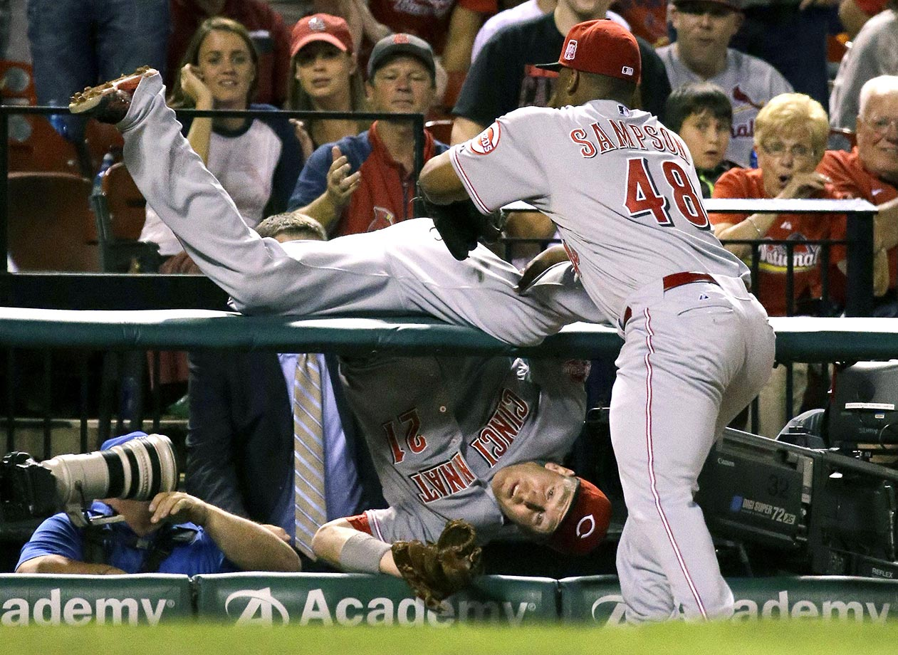 Todd Frazier of the Cincinnati Reds flips over the photo pit while going for a foul ball against the Cardinals.