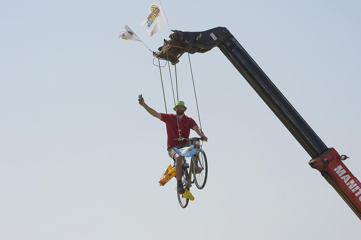 A Tour de France fan is suspended from a crane during the sixth stage of the race.
