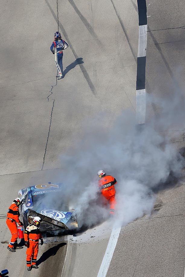 Trevor Bayne strolls away as the safety crew extinguishes flames on his car.