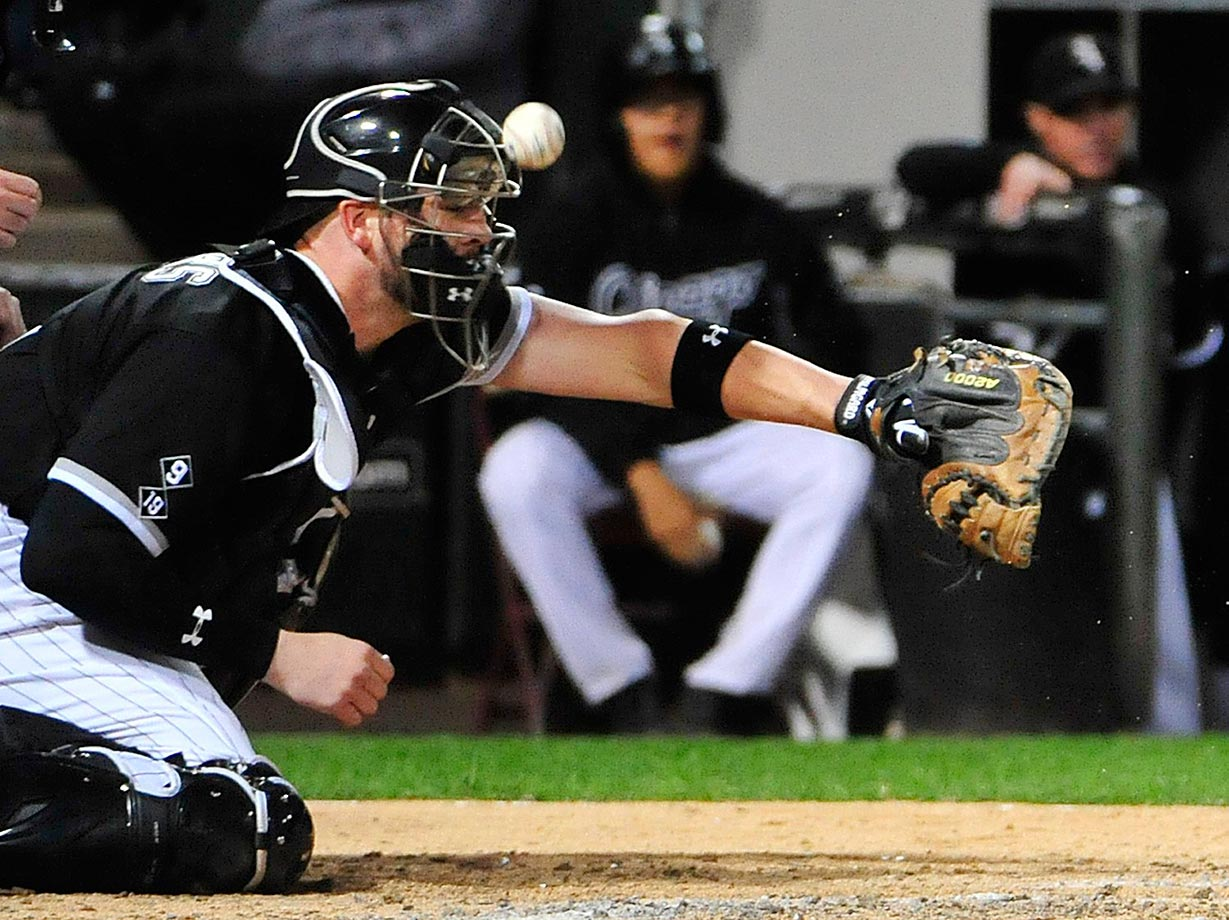 Tyler Flowers of the Chicago White Sox takes a foul ball off his mask during a Royals game.