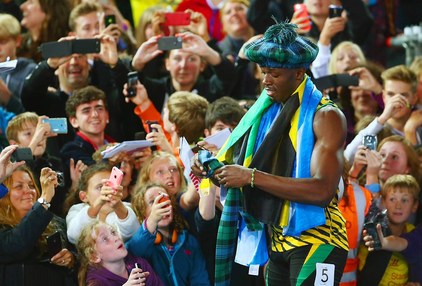 Usain Bolt of Jamaica greets fans as he celebrates winning gold in the Men's 4x100 metres relay final at Hampden Park during Day Ten of the Glasgow 2014 Commonwealth Games on August 2, 2014 in Glasgow, United Kingdom.