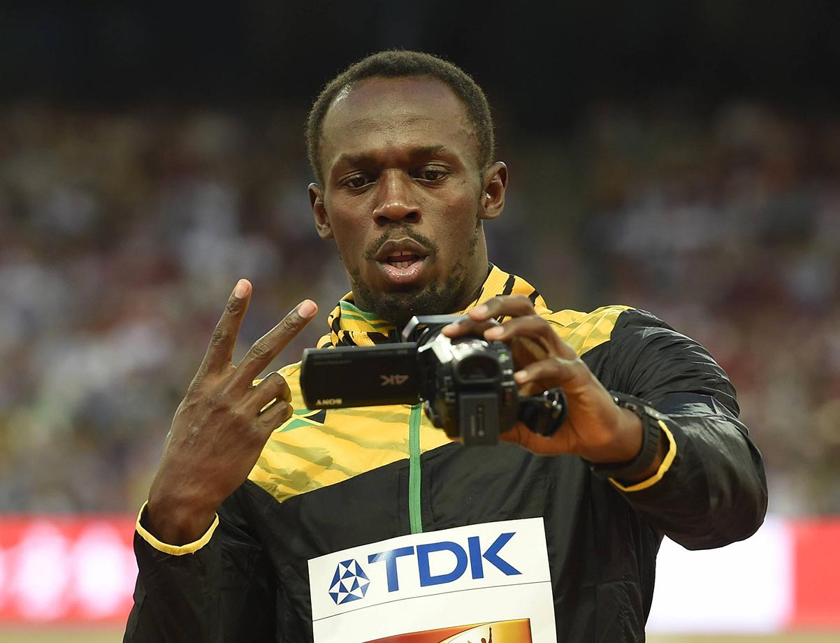Usain Bolt films himself during the awards ceremony of the 100-meter event at the 2015 IAAF World Championships.