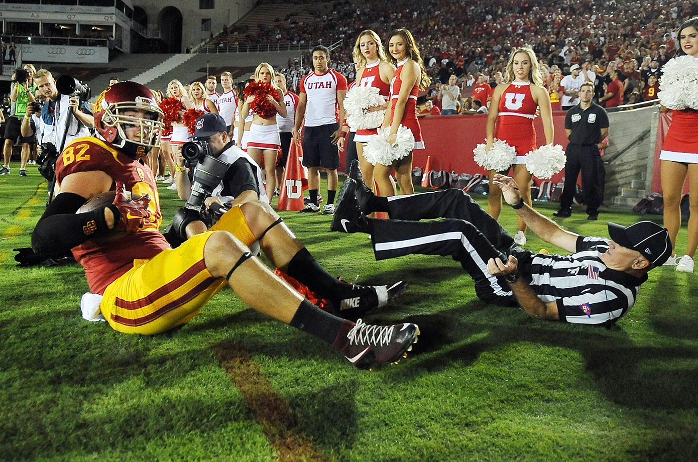 Tyler Petite of USC takes out a referee after being forced out of bounds in a game against Utah.