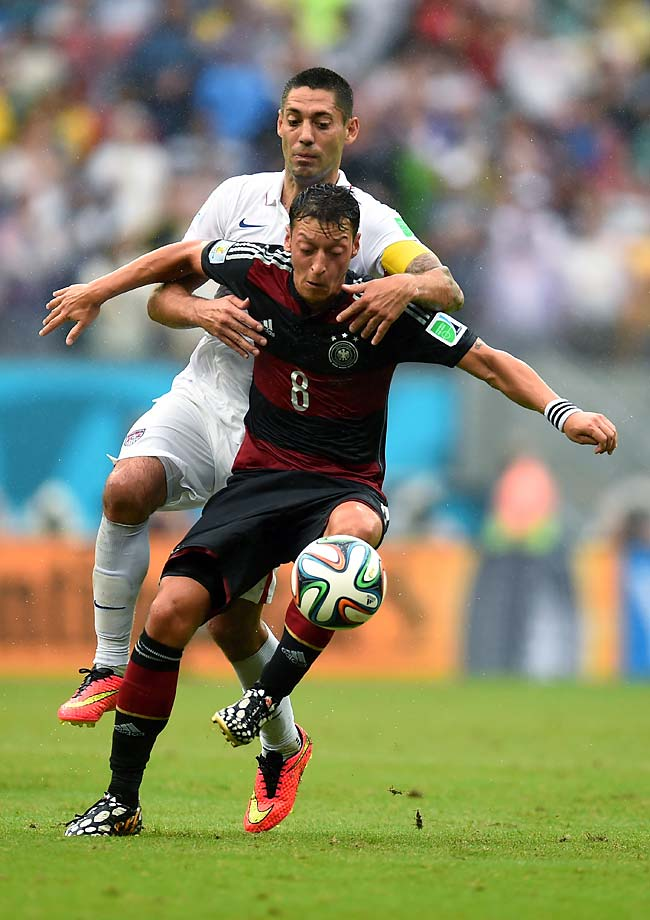 Clint Dempsey and Mesut Oezil compete for the ball.