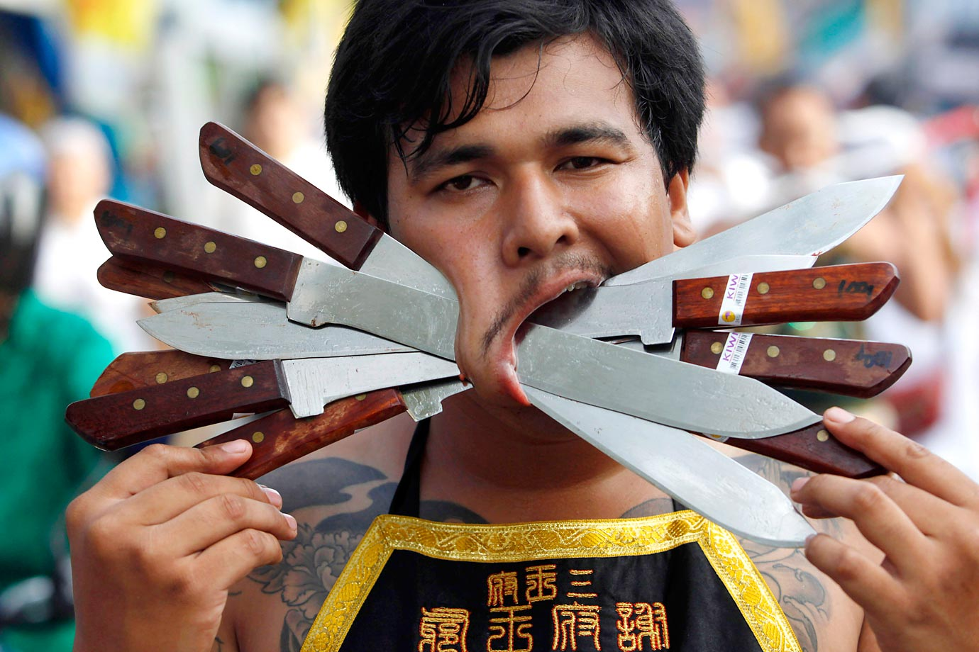 A vegetarian festival devotee parades through the streets in Phuket, Thailand. Participants in the festival perform acts of body piercing as a means of shifting evil spirits from individuals onto themselves and bring the community good luck.