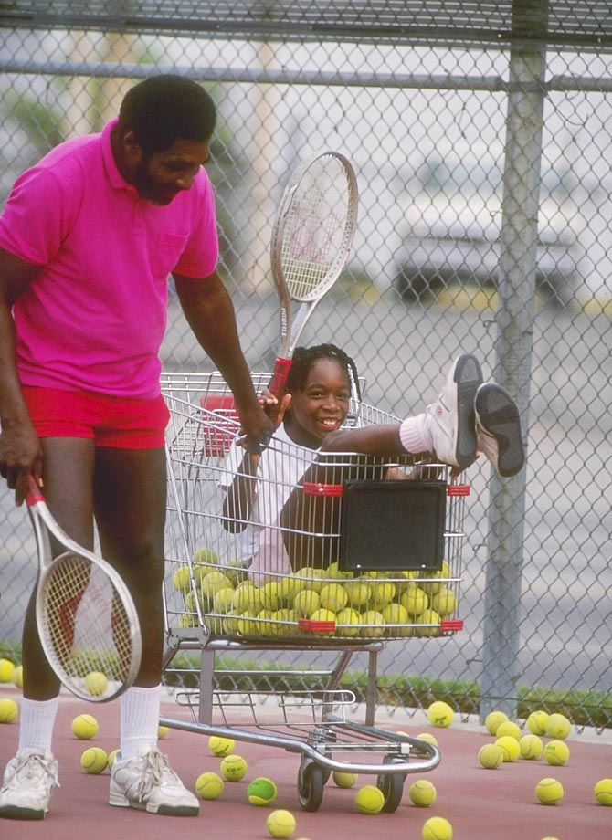 "Williams is pushed in a shopping cart by her father, Richard Williams, during practice. Richard promised coach Rick Macci that Williams was the next Jennifer Capriati, but Macci didn't believe Richard. It wasn't Williams' tennis ability that originally impressed Macci, it was her athleticism—she walked 10 yards on her hands and did backward cartwheels, leading him to feel that he had a ""female Michael Jordan on [his] hands."""