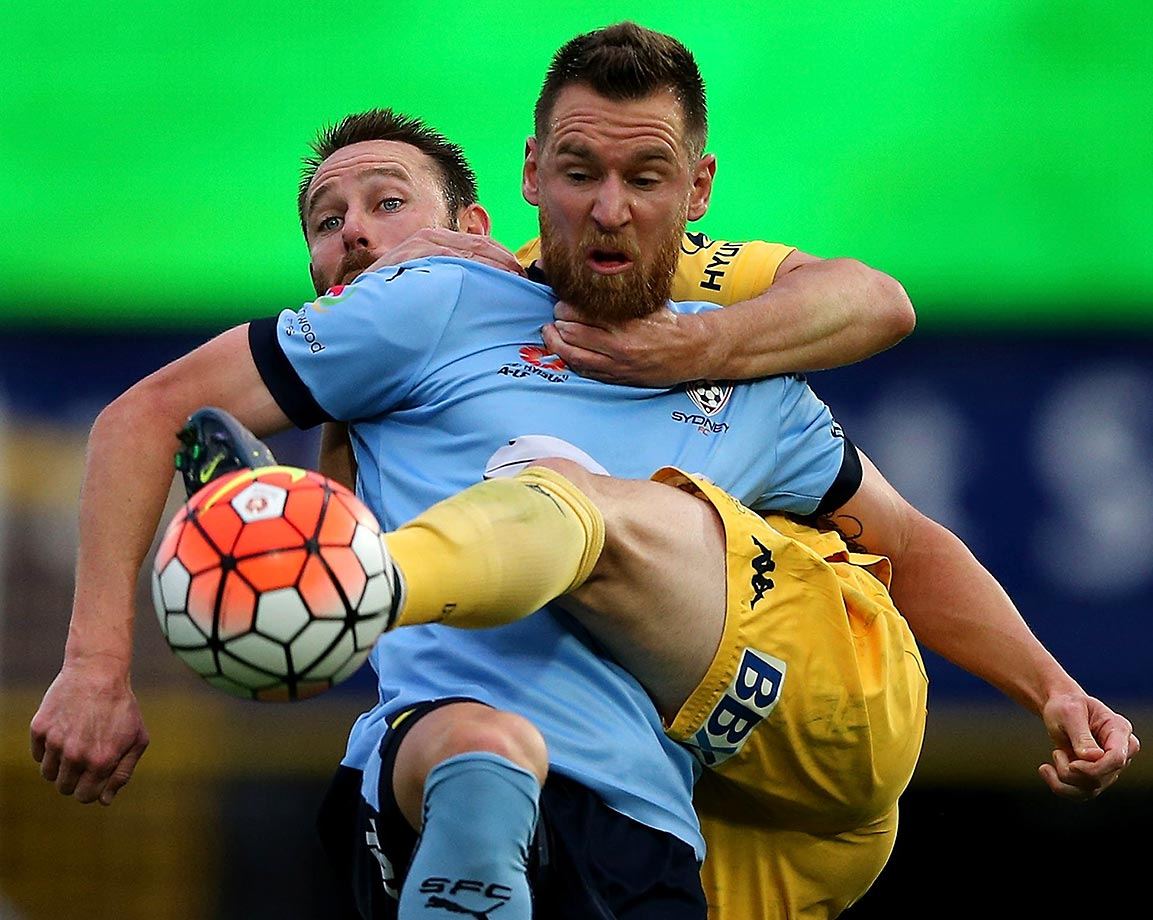 Shane Smeltz goes against Joshua Rose during the round four A-League match between the Central Coast Mariners and Sydney FC.