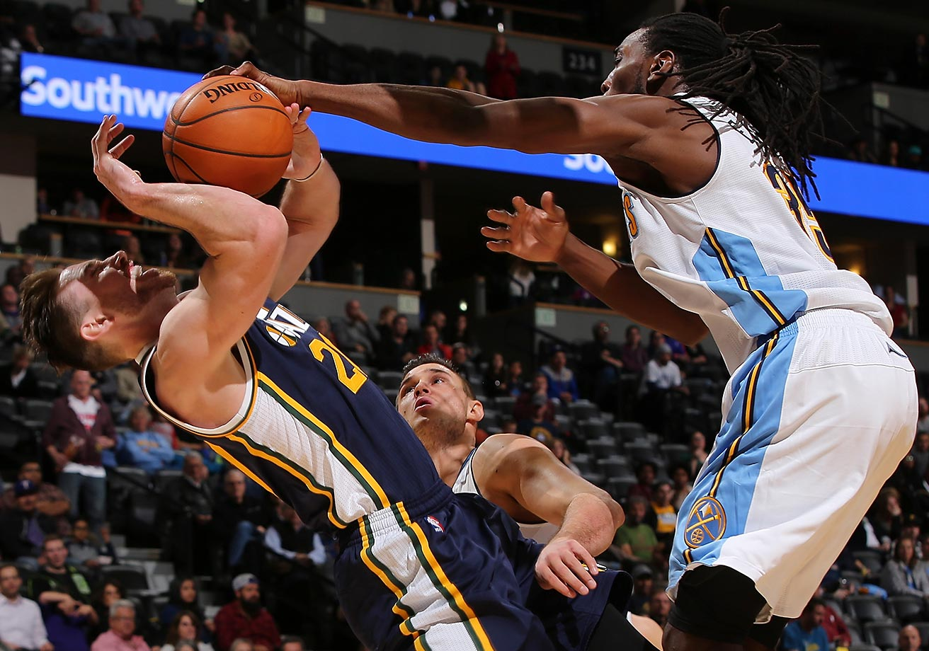 Gordon Hayward of the Utah Jazz is fouled by Kenneth Faried of the Denver Nuggets.
