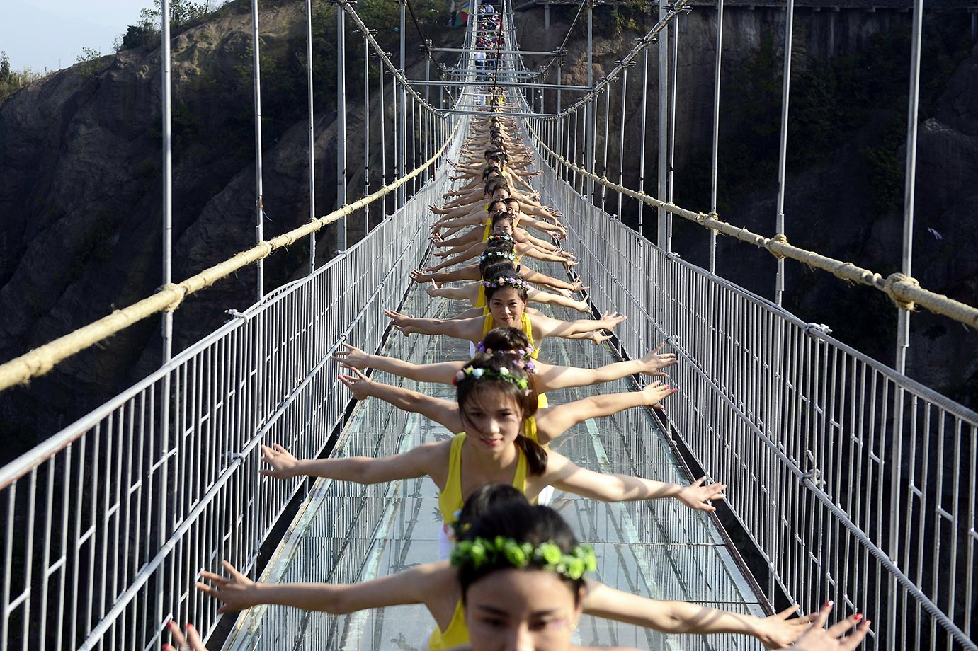 Chinese yoga fans perform on a glass-bottomed suspension bridge in the Shiniuzhai mountains in Pingjiang county, central China's Hunan province.