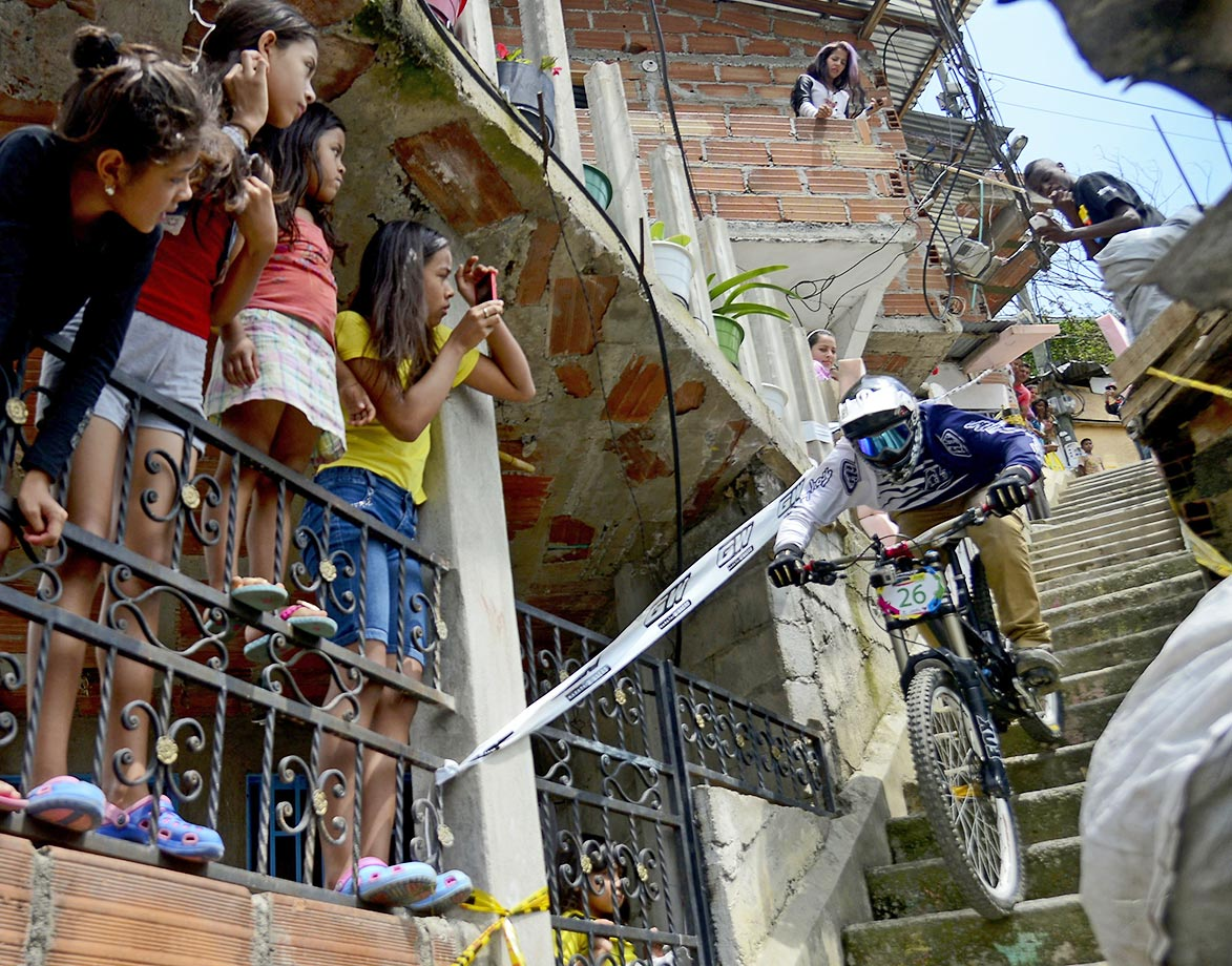 Children watch as a downhill rider competes in the Adrenalina Urban Bike race final in Medellin.